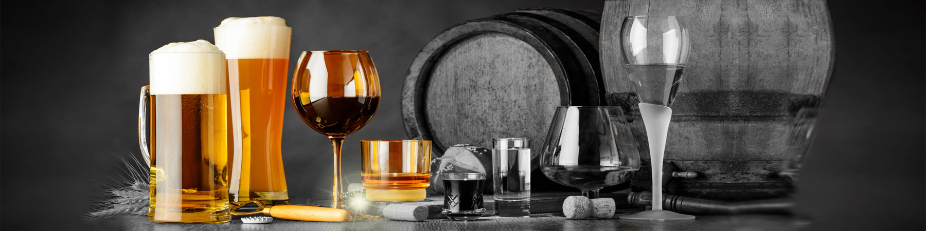 alcoholic drinks on wooden table in glasses, mugs and shots with barrel in background