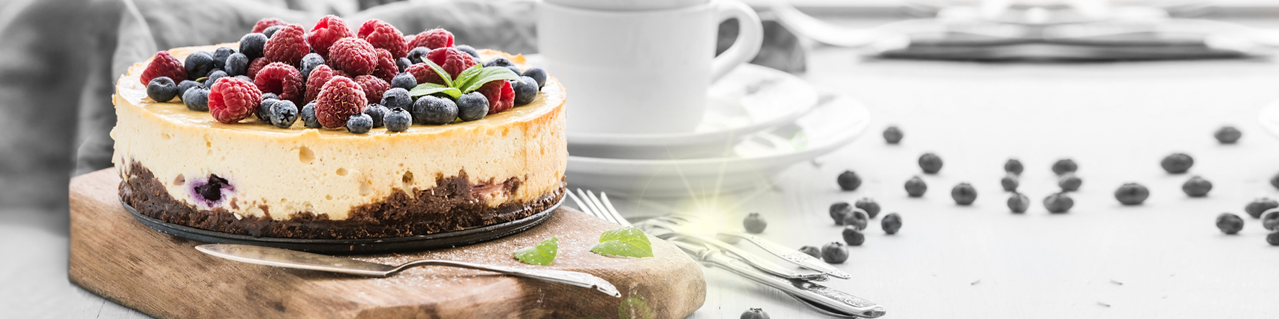 Cheesecake with fresh raspberries and blueberries on a wooden serving board, plates, cups, kitchen napkin, silverware over blue background, window at the backdrop